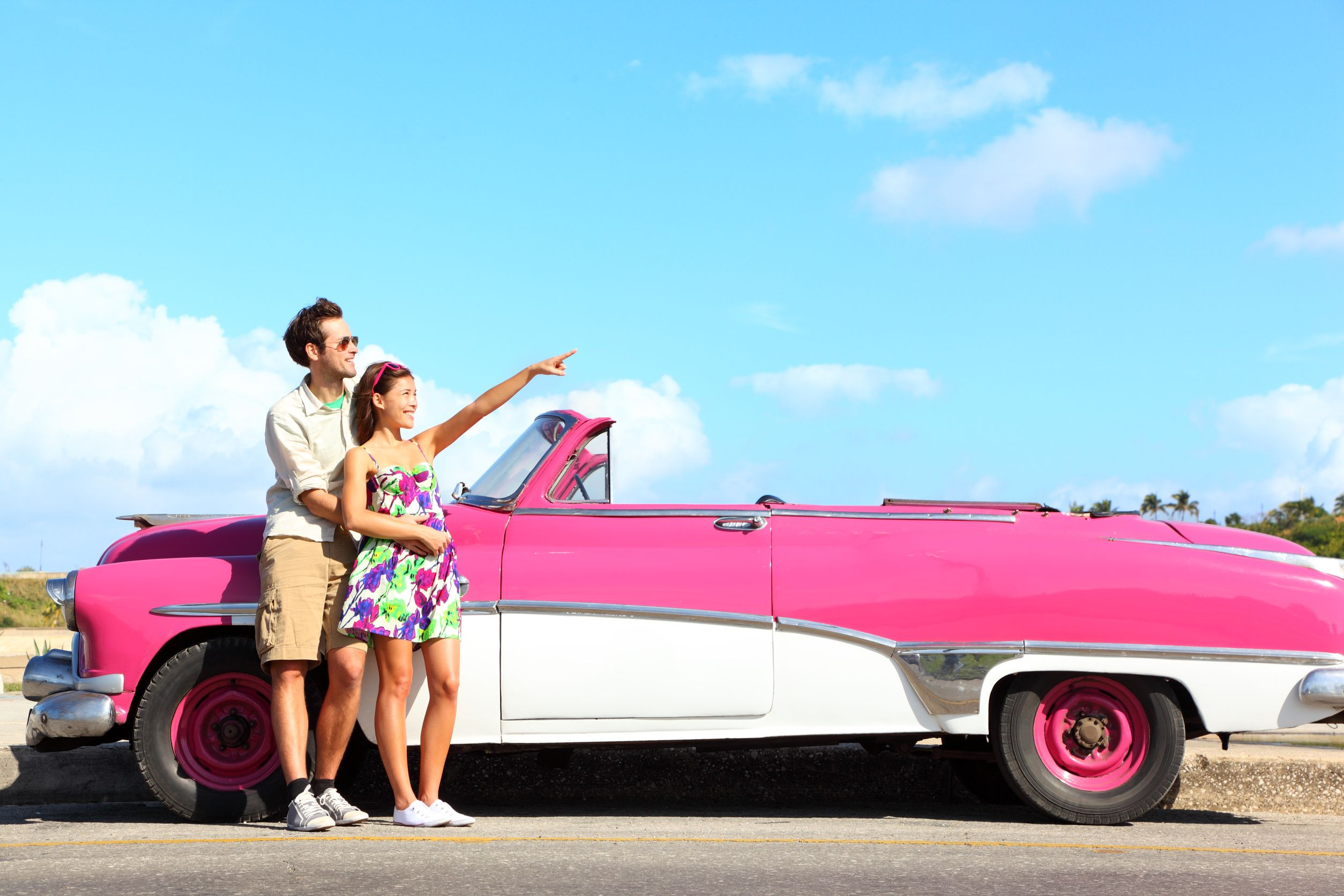 vintage-car-couple-pointing-looking-standing-by-pink-retro-vintage-car-smiling-happy-young-couple-on-summer-road-trip-car-holiday-in-Havana-Cuba
